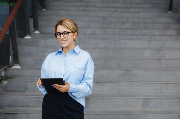 Atrakcyjna młoda dama z blond włosami za pomocą cyfrowego tabletu stojąc na schodach w pobliżu biurowca. koncepcja ludzie, biznes i nowoczesna technologia.
