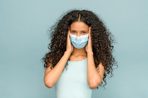Atrakcyjna młoda dominikanka z długimi kręconymi włosami w masce na twarz podczas koronawirusa