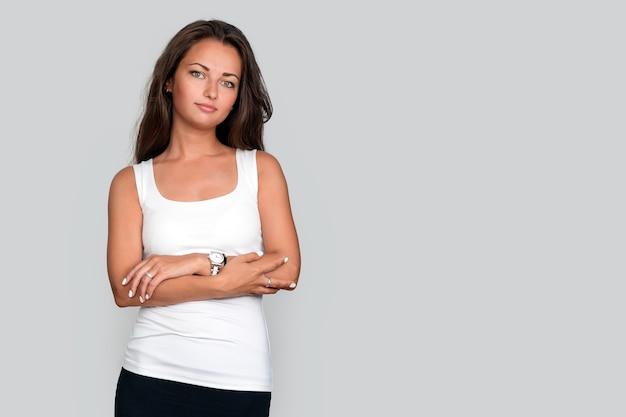 Atrakcyjna młoda dopasowana kobieta na szarym tle studia, dorywczo kobieta skrzyżowana ręka wygląda zdrowo i pewnie w białym podkoszulku bez rękawów, bezpłatne miejsce na tekst.