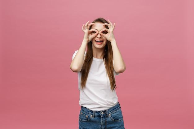 Atrakcyjna, młoda, dorosła kobieta pokazuje znak ok