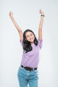 Atrakcyjna młoda dziewczyna azjatyckich uśmiecha się szczęśliwie patrząc, zaciskając w pięści i podniósł dwie ręce