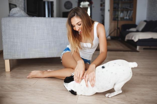 Atrakcyjna młoda dziewczyna bawić się z psem na podłoga przy żywym pokojem