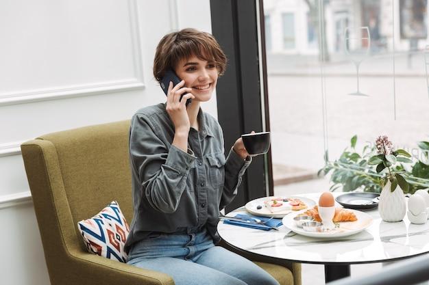 Atrakcyjna młoda dziewczyna je śniadanie w kawiarni w pomieszczeniu, rozmawia przez telefon komórkowy
