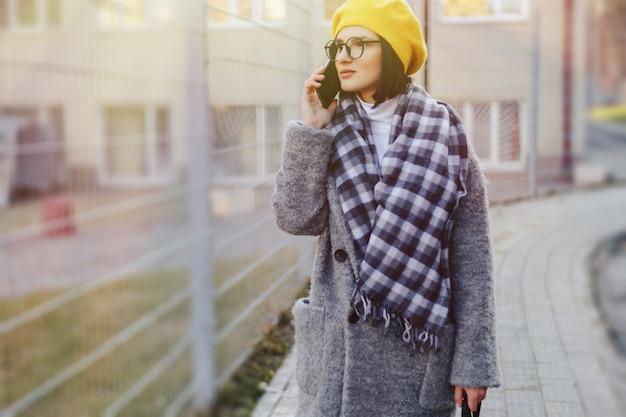 Atrakcyjna młoda dziewczyna nosi okulary w płaszczu idąc ulicą