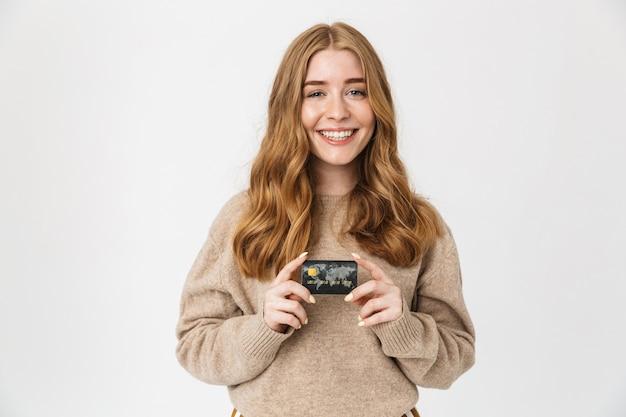 Atrakcyjna młoda dziewczyna nosi sweter stojący na białym tle nad białą ścianą, pokazując plastikową kartę kredytową
