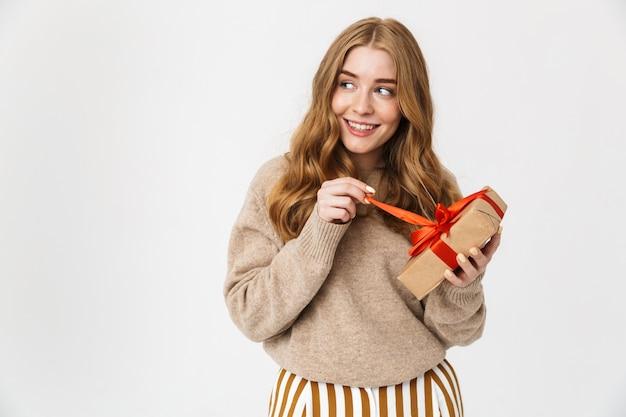 Atrakcyjna młoda dziewczyna nosi sweter stojący na białym tle nad białą ścianą, pokazując pudełko na prezent