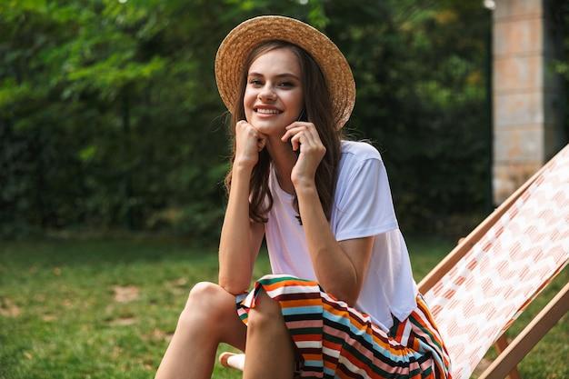 Atrakcyjna młoda dziewczyna odpoczywa na hamaku w parku miejskim na świeżym powietrzu latem