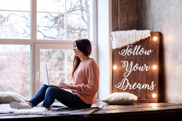 Atrakcyjna młoda dziewczyna pracuje lub studiuje w domu za pomocą swojego laptopa. podążaj za marzeniami motywacyjnymi napisanymi na tablicy.