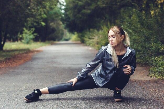 Atrakcyjna młoda dziewczyna robi rozciągających ćwiczeń sportowych w parku miejskim przy deszczowej pogodzie.