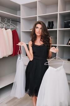 Atrakcyjna młoda dziewczyna stoi w garderobie i nie może dokonać wyboru między dwiema spódnicami, w zamyśleniu patrzy na bok. ubrana jest w czarną sukienkę. prawdziwe emocje