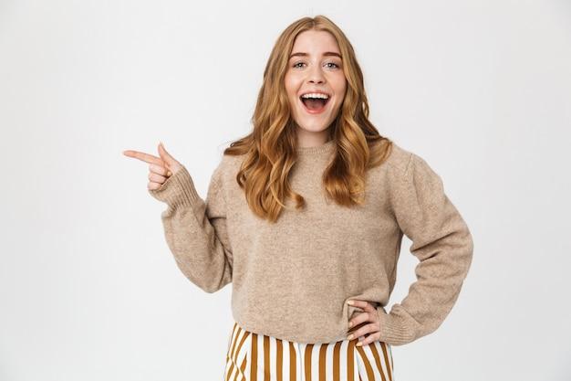 Atrakcyjna młoda dziewczyna ubrana w sweter stojący na białym tle nad białą ścianą, wskazująca na miejsce na kopię