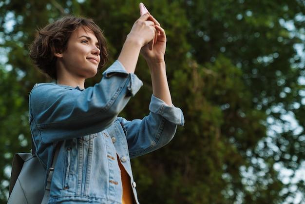 Atrakcyjna młoda dziewczyna ubrana w swobodny strój, spędzająca czas na świeżym powietrzu w parku, robiąca zdjęcia telefonem komórkowym