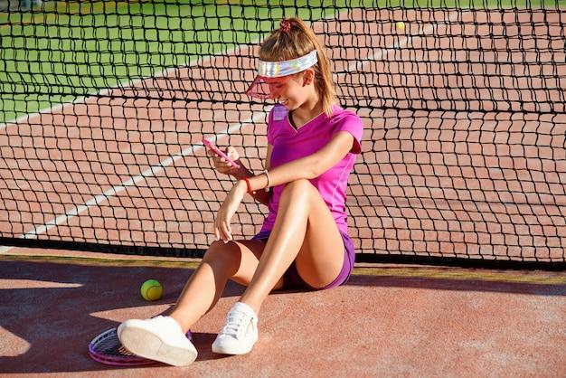 Atrakcyjna młoda dziewczyna w odzieży sportowej, siedząc na korcie tenisowym w pobliżu sieci i co selfie zdjęcie na telefon o zachodzie słońca. relaks po treningu tenisowym.