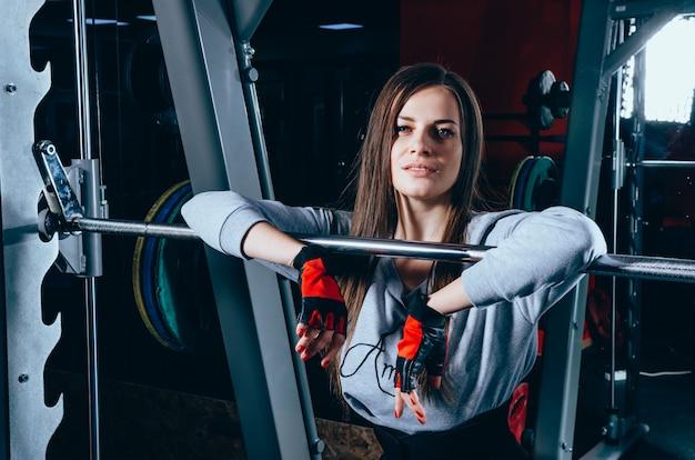 Atrakcyjna młoda dziewczyna w odzieży sportowej stoi w pobliżu sztangi na siłowni