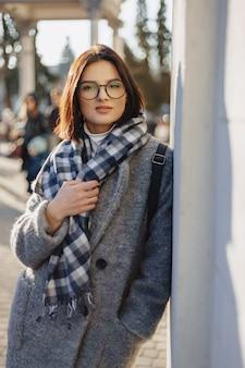 Atrakcyjna młoda dziewczyna w okularach w płaszczu chodzenie w słoneczny dzień