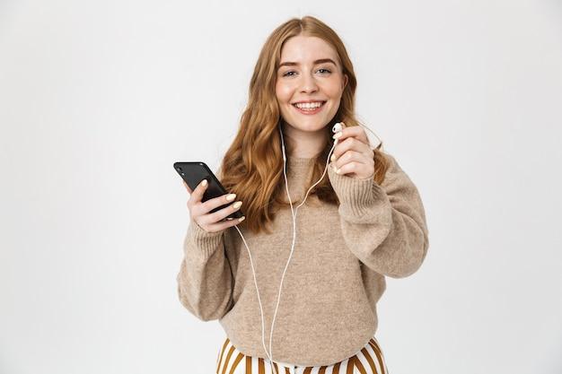 Atrakcyjna młoda dziewczyna w swetrze stojąca na białym tle nad białą ścianą, słuchająca muzyki przez słuchawki, trzymająca telefon komórkowy