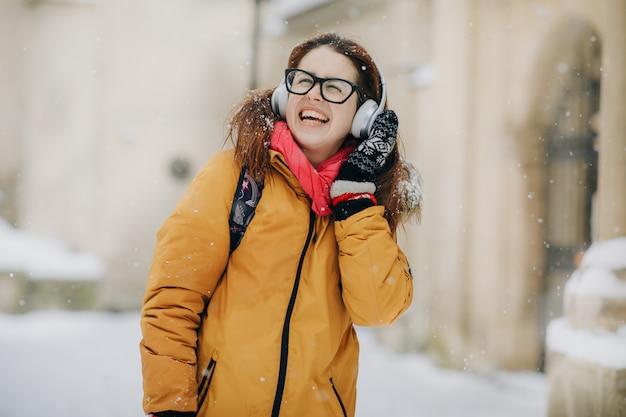 Atrakcyjna młoda dziewczyna wyjazd do miasta i słuchanie muzyki przez telefon. stylowy wygląd, swobodne akcesoria. modny wygląd