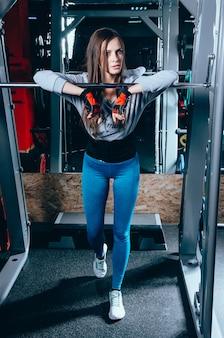 Atrakcyjna młoda dziewczynka kaukaski w sporcie nosić stoi w pobliżu sztangi na siłowni