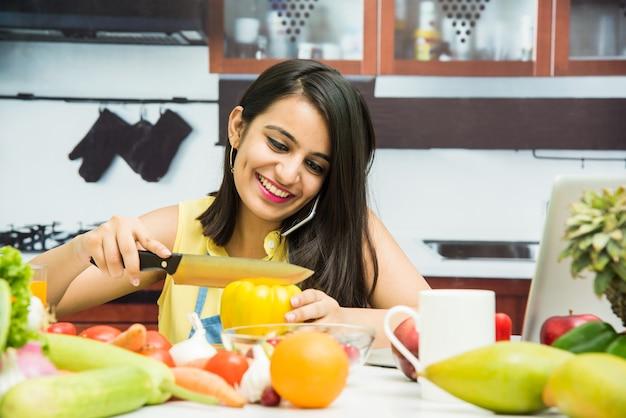Atrakcyjna młoda indyjska dziewczyna lub kobieta z fartuchem w kuchni wielozadaniowości, przy użyciu smartfona, tabletu pc ze stołem pełnym owoców i warzyw oraz komputera