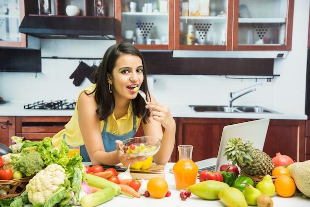 Atrakcyjna młoda indyjska dziewczyna w fartuchu gotuje w kuchni ze stołem pełnym owoców i warzyw