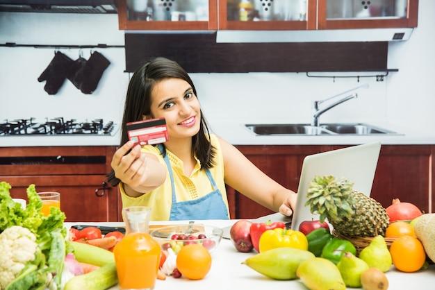 Atrakcyjna młoda indyjska dziewczyna z fartuchem w kuchni zakupy online za pomocą karty debetowej lub kredytowej na laptopie ze stołem pełnym świeżych owoców i warzyw