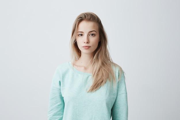 Atrakcyjna młoda kaukaska ciemnooka kobieta z długimi farbowanymi blond włosami pozującymi na szarej pustej ścianie, ubrana w swobodny niebieski sweter o spokojnym wyrazie twarzy.
