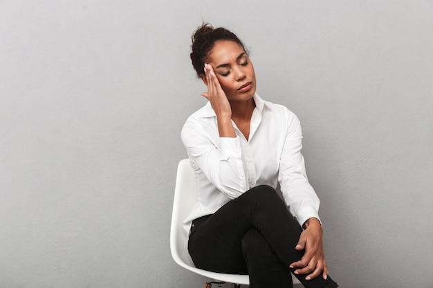 Atrakcyjna młoda kobieta afrykańskiego biznesu na sobie koszulę siedzi na krześle na białym tle, cierpi na ból głowy