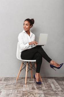 Atrakcyjna młoda kobieta afrykańskiego biznesu na sobie koszulę siedzi na krześle na białym tle, pracując na laptopie