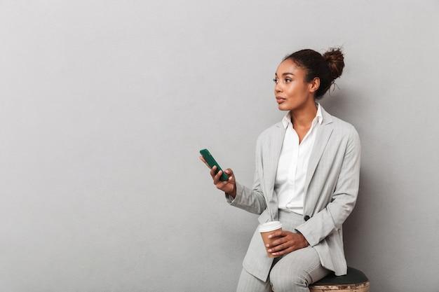 Atrakcyjna młoda kobieta afrykańskiego biznesu siedzi na krześle na białym tle, przy użyciu telefonu komórkowego, trzymając filiżankę kawy na wynos