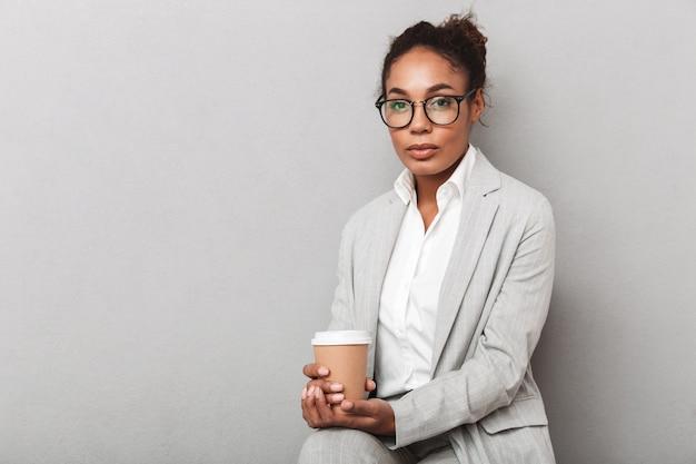 Atrakcyjna młoda kobieta afrykańskiego biznesu siedzi na krześle na białym tle, trzymając filiżankę kawy na wynos
