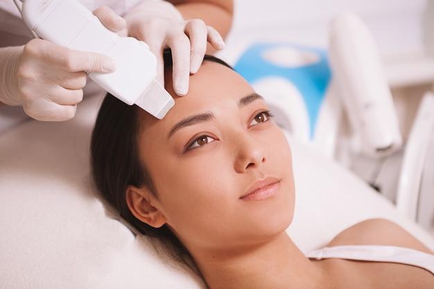 Atrakcyjna młoda kobieta azji po oczyszczeniu skóry przez kosmetologa za pomocą aparatu kawitacyjnego ultradźwiękowego