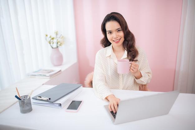 Atrakcyjna młoda kobieta azji za pomocą laptopa podczas picia herbaty / kawy.