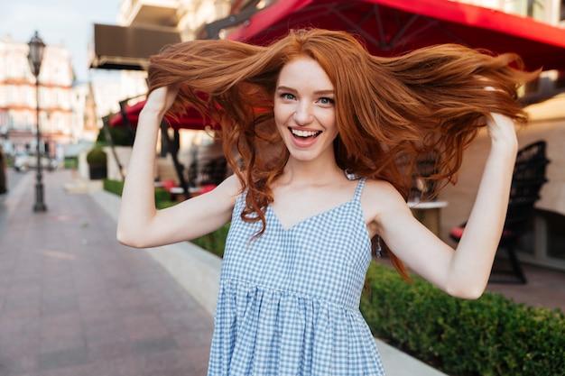 Atrakcyjna młoda kobieta bawić się z jej włosy
