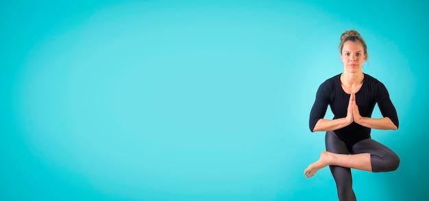 Atrakcyjna młoda kobieta ćwicząca na niebieskim tle wysportowana kobieta robi ćwiczenia sport