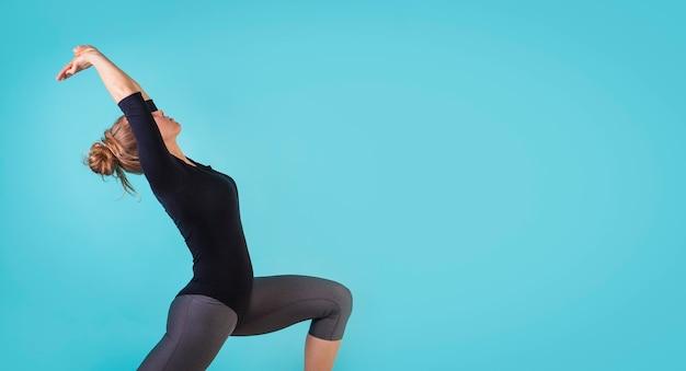 Atrakcyjna młoda kobieta ćwicząca taniec na niebieskim tle kobieta robi ćwiczenia wolne miejsce