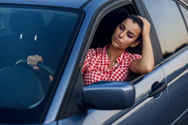 Atrakcyjna młoda kobieta czerpie przyjemność z prowadzenia samochodu.