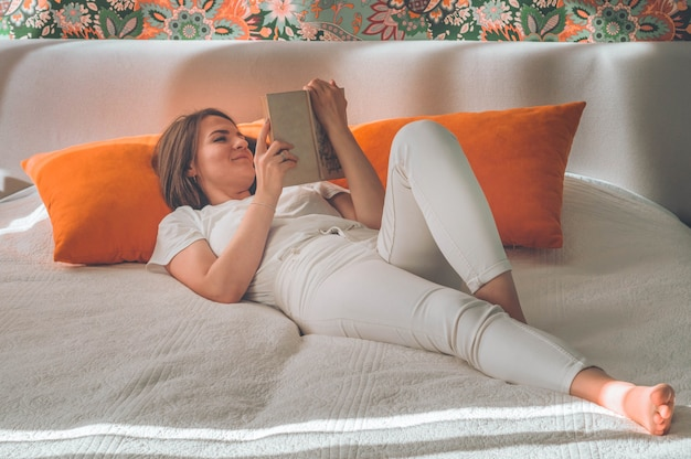 Atrakcyjna młoda kobieta czyta książkę w domu