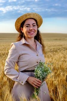 Atrakcyjna młoda kobieta długowłosa w słomkowym kapeluszu, uśmiechając się i trzyma bukiet dzikich kwiatów w polu pszenicy o wschodzie słońca.