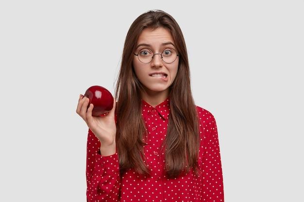 Atrakcyjna młoda kobieta gryzie wargi dolne wargi, trzyma świeże czerwone jabłko, ma zdrowe odżywianie, nosi czerwoną koszulę w kropki, stoi na białym tle