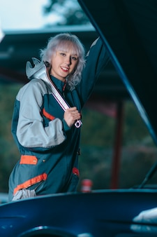 Atrakcyjna młoda kobieta jako auto mechanik pozuje z kluczem w garażu