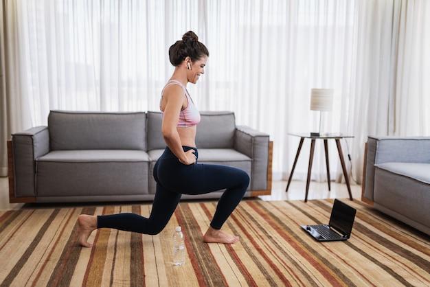 Atrakcyjna młoda kobieta łacińskiej robi joga rozciągania jogi online w domu.
