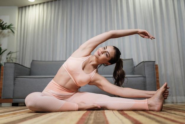 Atrakcyjna młoda kobieta łacińskiej robi joga rozciągania jogi w domu. pojęcie zdrowego stylu życia.