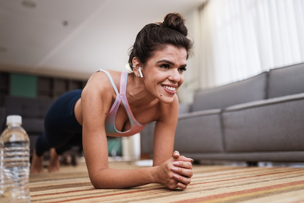 Atrakcyjna młoda kobieta łacińskiej robi joga rozciągania jogi w domu.