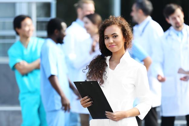 Atrakcyjna młoda kobieta lekarz ze schowka w ręce przeciwko grupie lekarzy