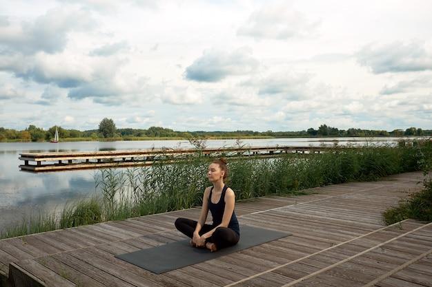 Atrakcyjna młoda kobieta lub model medytacji i praktykowania jogi na molo w pobliżu jeziora.