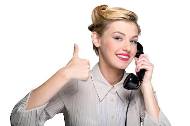 Atrakcyjna młoda kobieta mówiąca na vintage telefon z kciukiem do góry