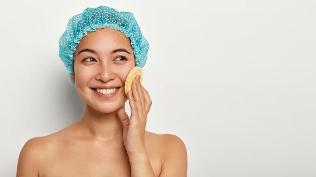 Atrakcyjna młoda kobieta myje twarz gąbką, dotyka policzka, patrzy na bok, nosi czepek, ma przyjemny wygląd
