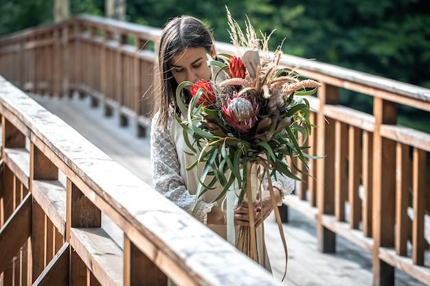 Atrakcyjna młoda kobieta na drewnianym moście stoi z bukietem egzotycznych kwiatów.