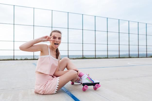 Atrakcyjna młoda kobieta na rolkach siedzi i zabawy na placu zabaw
