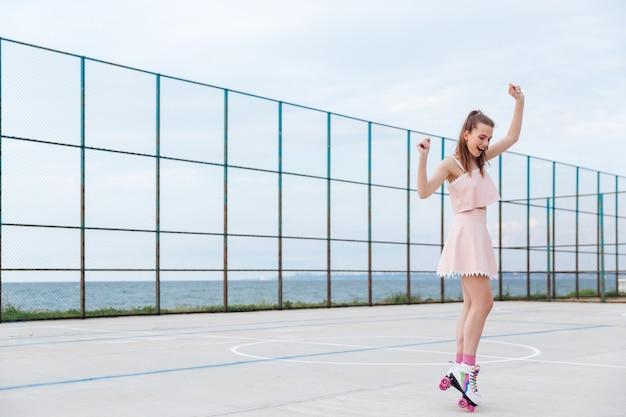 Atrakcyjna młoda kobieta na rolkach stojąc i zabawy na placu zabaw